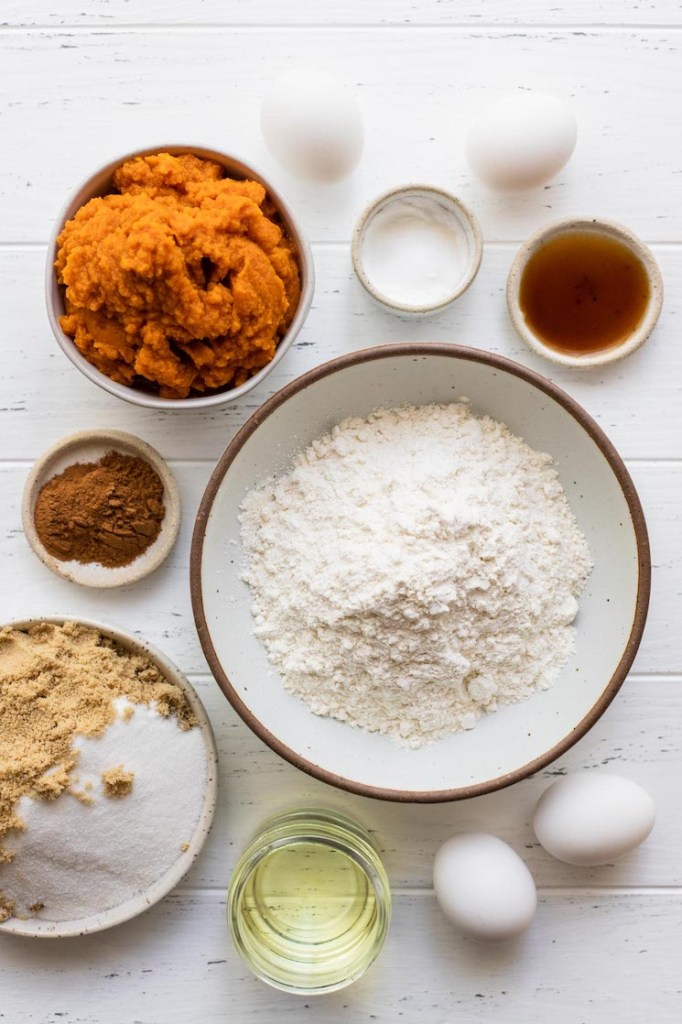 The ingredients needed to make pumpkin cake on a rustic white wood surface.