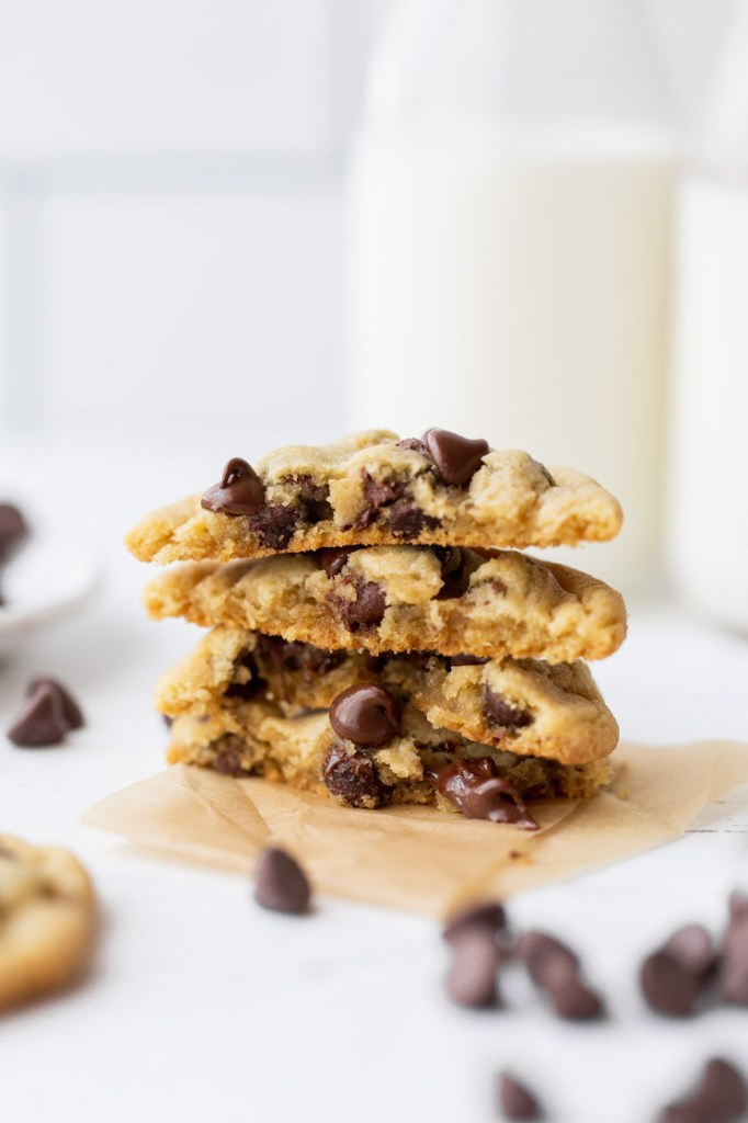 A stack of chocolate chip cookies cut in half showing the inside texture and melty chocolate chips.