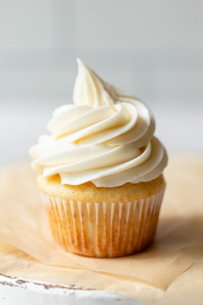 Um único cupcake coberto com cobertura de creme de manteiga em cima de papel pergaminho castanho.