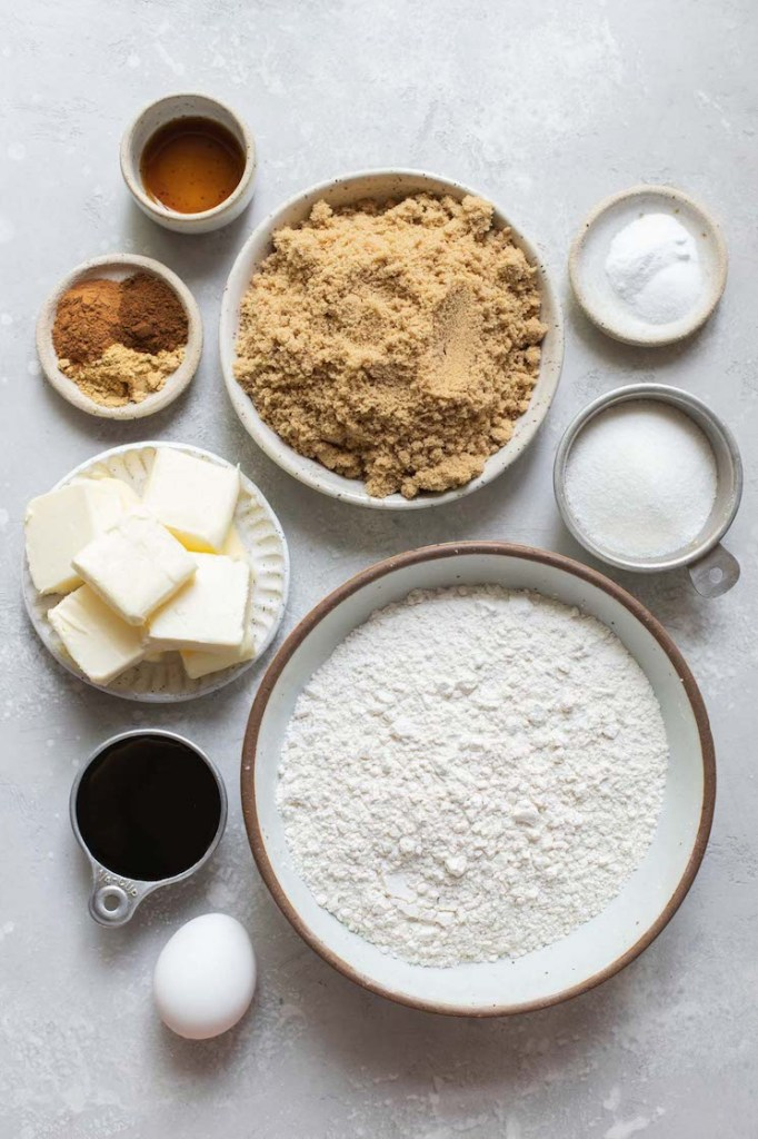 The ingredients needed to make cookies laid out in bowls on top of a rustic gray surface.