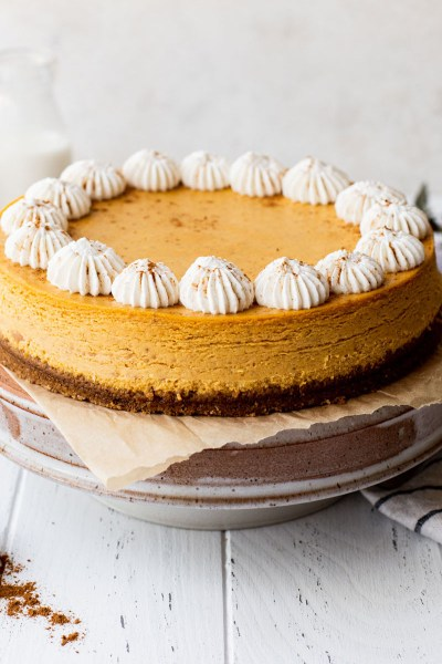 A pumpkin cheesecake on top of a cake stand with milk and cinnamon around it.