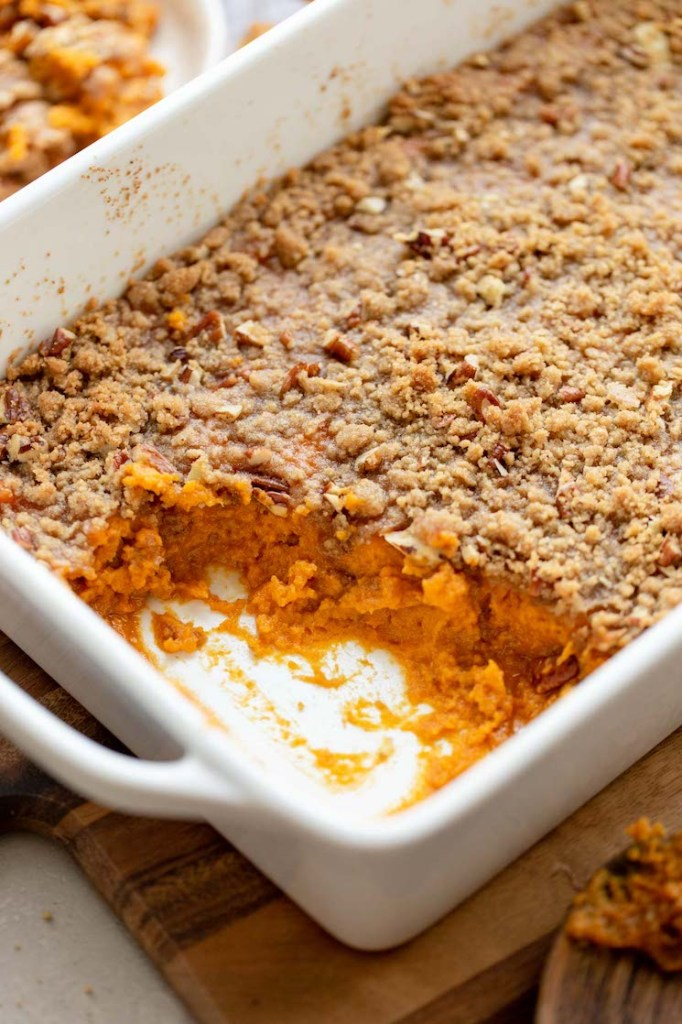 A sweet potato casserole in a baking dish with one corner scooped out to show the sweet potato base.