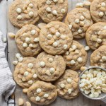 A batch of cookies laid out on a piece of parchment paper with extra nuts and white chocolate chips beside them.