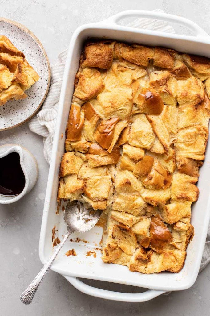 An overhead view of bread pudding in a 9x13 pan. A slice of bread pudding and small container of syrup rest beside it.