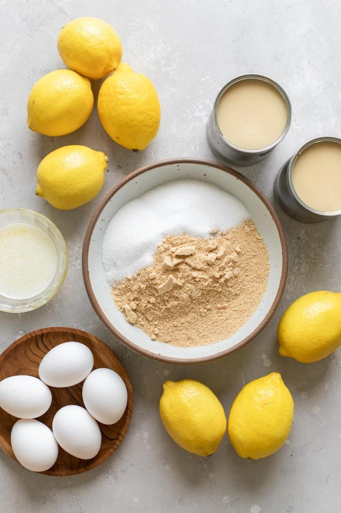 The ingredients needed to make lemon pie laid out on a gray surface.
