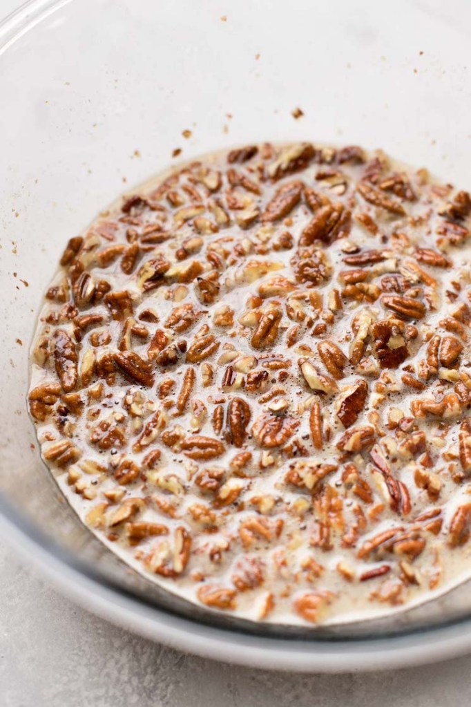 A glass mixing bowl holding pecan pie filling.