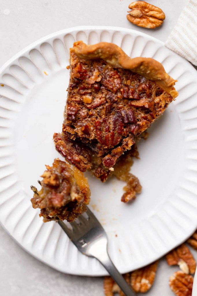 An individual slice of pecan pie on a white plate with a bite taken out on a fork.