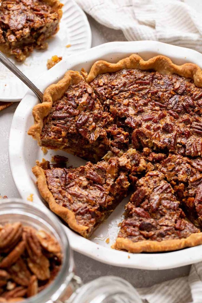 A pecan pie in a white dish that has been sliced and one slice is being removed.