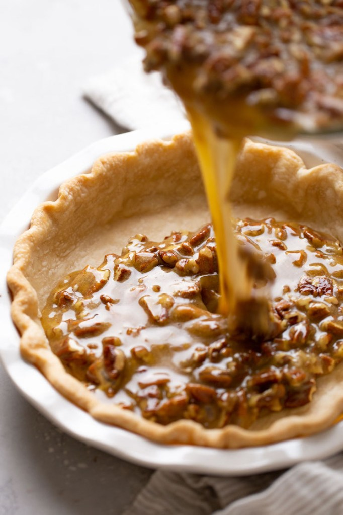 Pecan pie filling being poured into a pie crust.