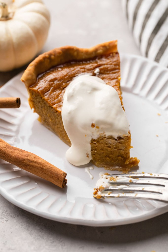 A slice of homemade pumpkin pie topped with whipped cream on a white plate.