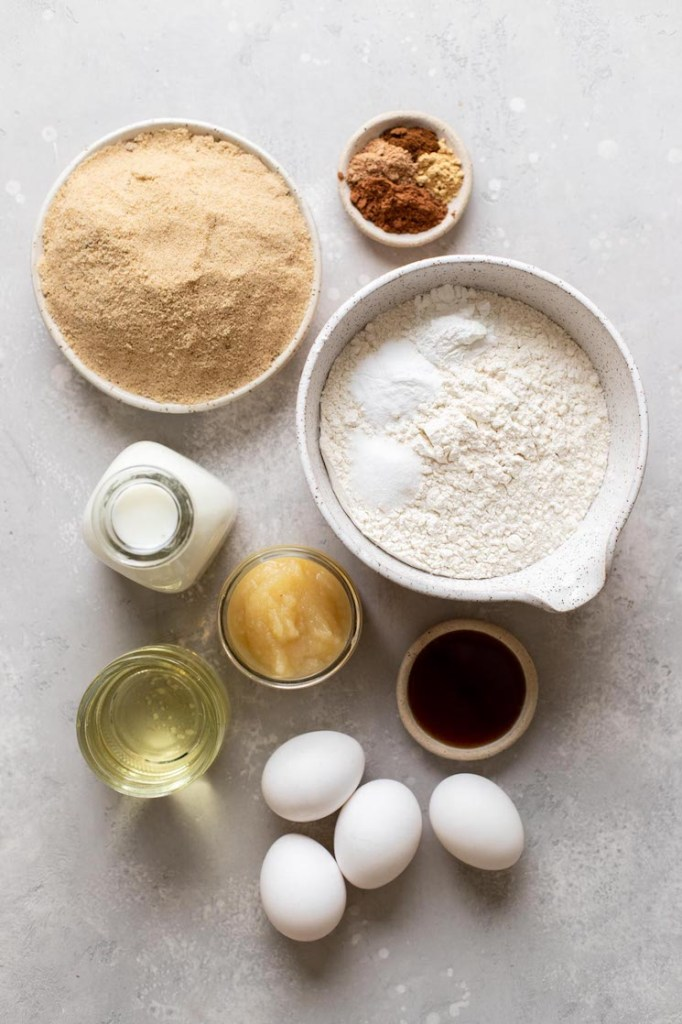The ingredients needed to make spice cake laid out on a gray surface.