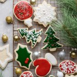A cooling rack filled with decorated cut out sugar cookies.