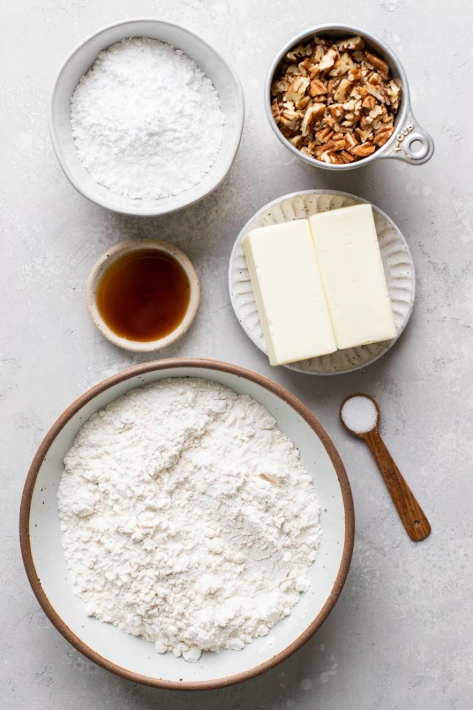 The ingredients needed to make snowball cookies laid out on a rustic gray surface.