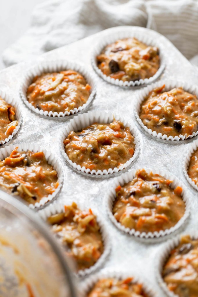 Unbaked morning glory muffins in a muffin tin, ready to be baked.