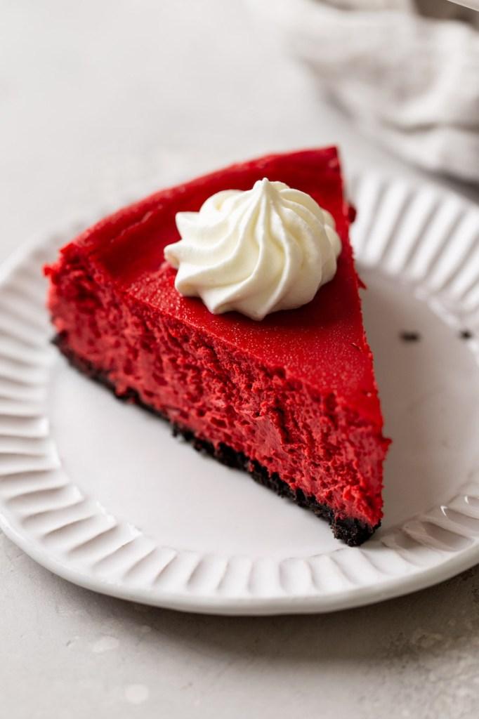 A slice of red velvet Oreo cheesecake on a white dessert plate.