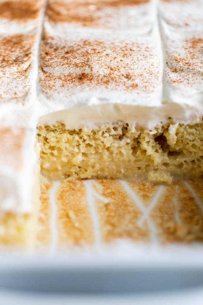 View into a pan of Mexican tres leches cake. A couple slices are missing from the front.