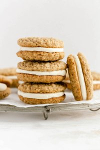 A stack of homemade oatmeal cream pies on a wire rack. One oatmeal cream pie is leaning up against the stack.