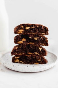 A stack of thick chocolate cookies with peanut butter chips on a white plate.