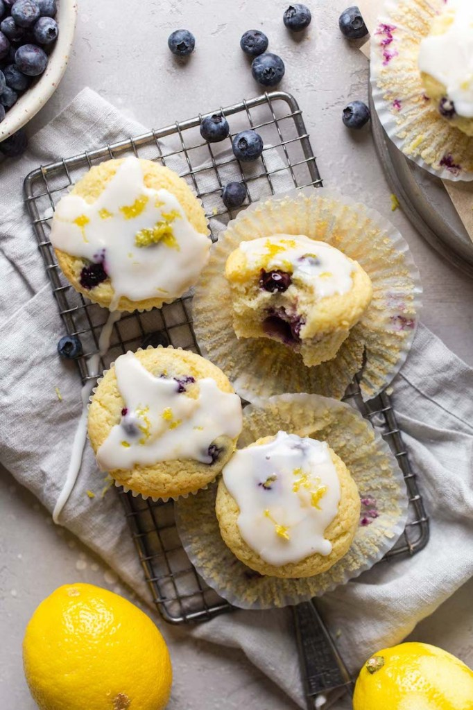 Overhead view of four lemon blueberry muffins on a wire rack. One muffin has a bite missing and is turned on its side. Lemons and fresh blueberries surround the muffins.