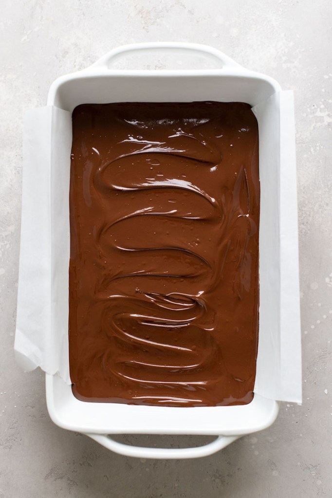 Overhead view of no bake chocolate peanut butter bars in a large baking dish. The bars have not yet set.