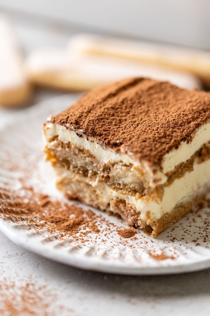 A slice of tiramisu on a white decorative plate. Three lady fingers rest in the background.