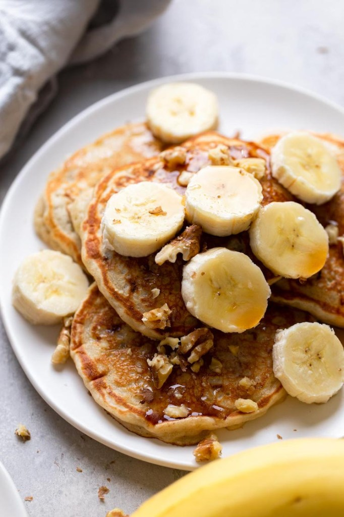 Four easy banana pancakes topped with syrup, banana slices, and walnuts on a white plate. A banana rests in the foreground.