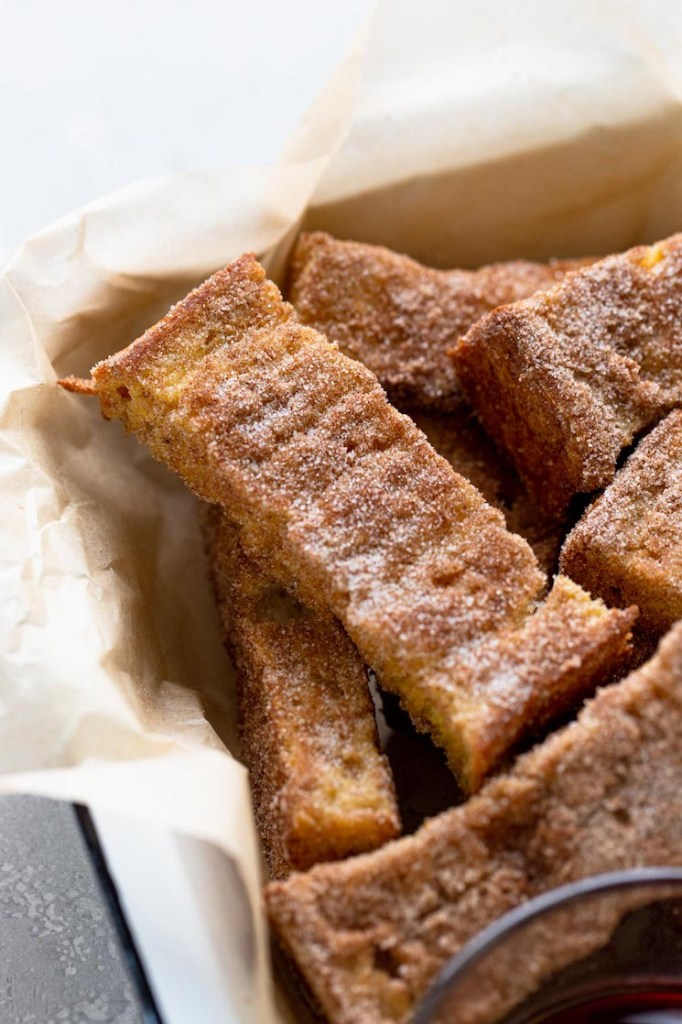 A pile of cinnamon french toast sticks in a baking dish lined with parchment paper.