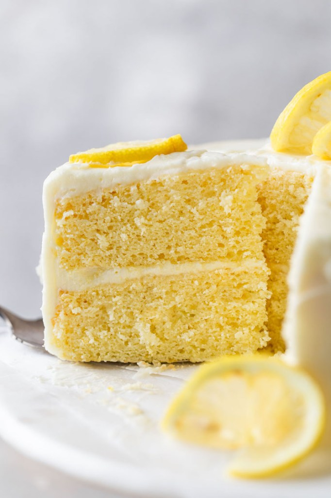 A side view of a slice of lemon cake being removed from a cake stand.