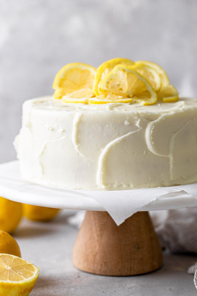 A side view of a lemon layer cake garnished with lemon slices on a white cake stand.