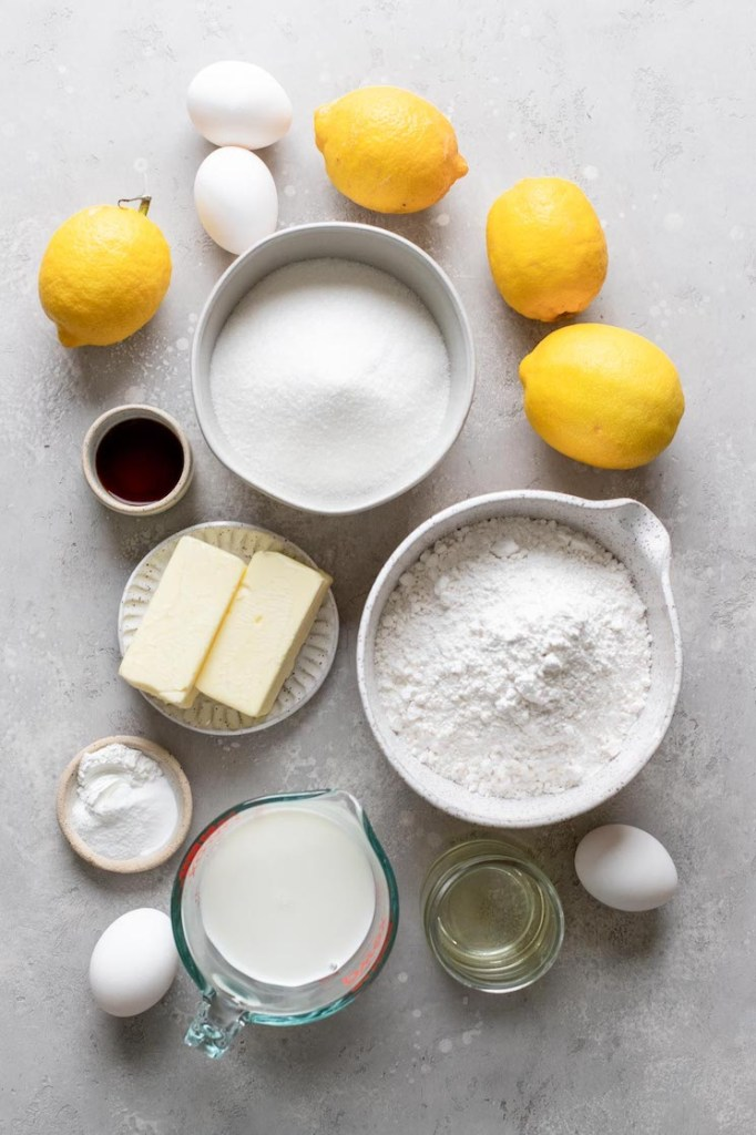 An overhead view of the ingredients needed to make a lemon cake from scratch.