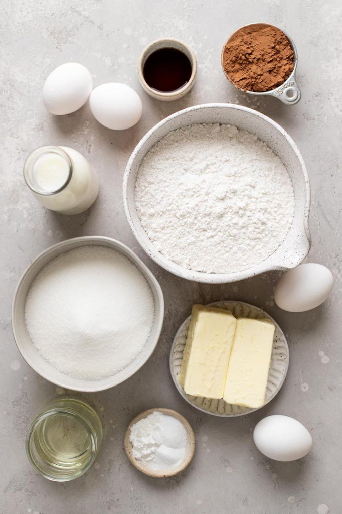 An overhead view of the ingredients needed to make a chocolate vanilla marble cake.