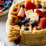 A tall stack of waffles topped with berries, butter, and syrup.