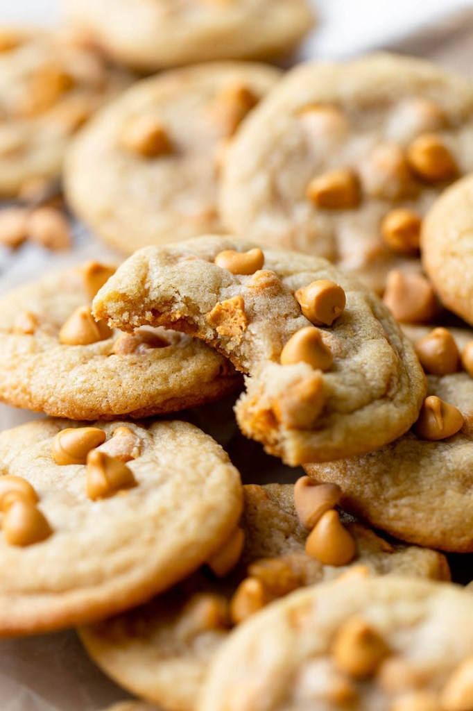 A pile of butterscotch chip cookies. The top cookie has a bite missing.