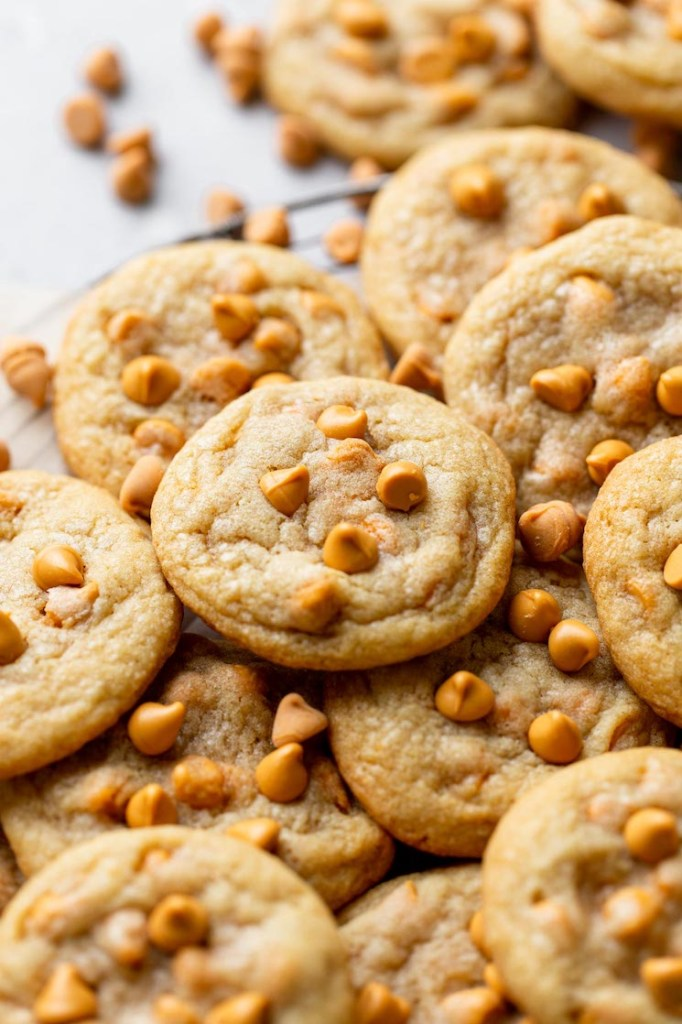 A close up view of butterscotch chip cookies piled on a wire cooling rack. Additional butterscotch chips are scattered in the background.