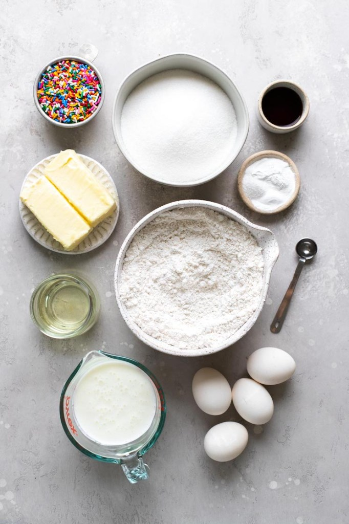 An overhead view of the ingredients needed to make funfetti cake from scratch.