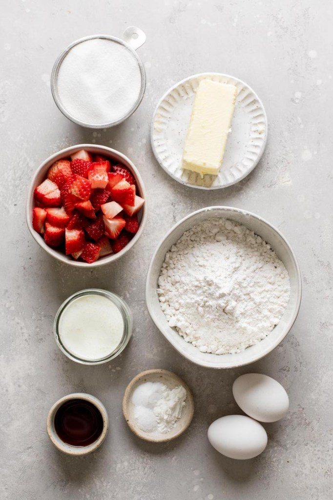 An overhead view of the ingredients needed to make strawberry cupcakes and strawberry frosting.
