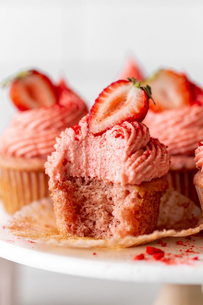 A close up view of cupcakes with strawberry frosting on a cake stand. The front cupcake has a bite missing.