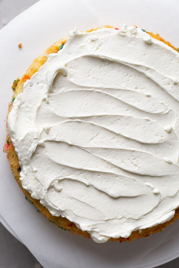 Overhead view of a cake layer topped with frosting.