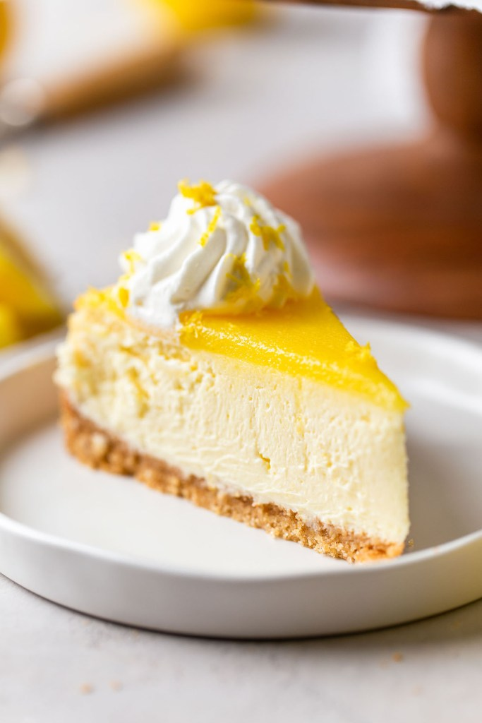 A slice of lemon cheesecake topped with lemon curd on a white dessert plate.