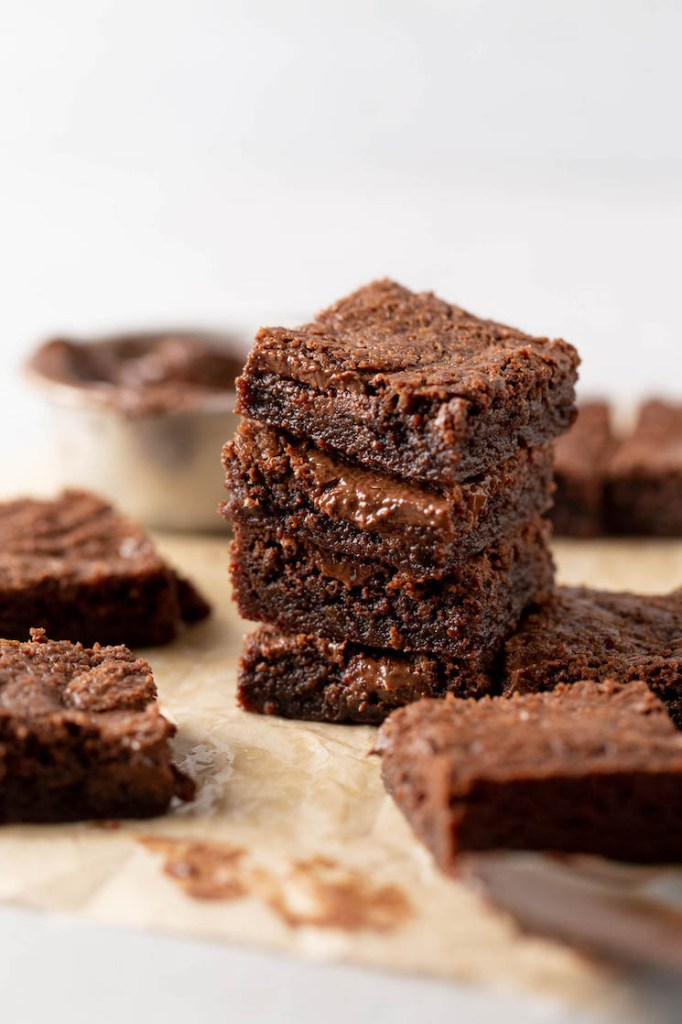 A stack of four brownies, with additional brownies scattered around.