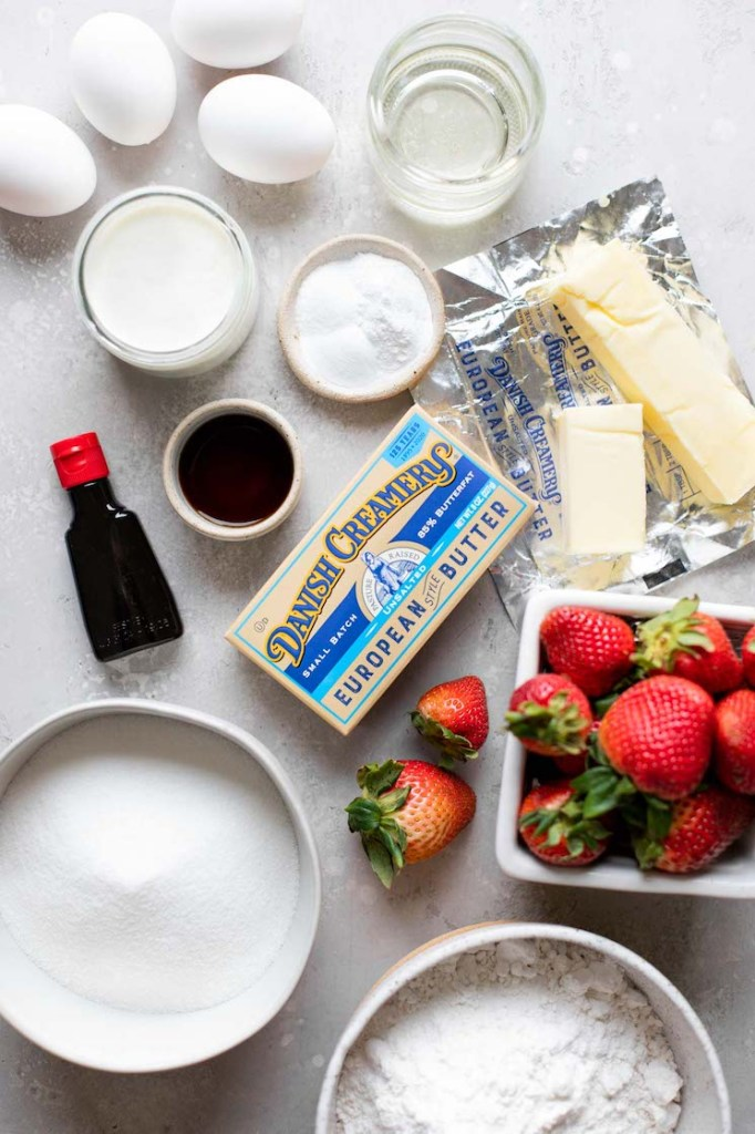 The ingredients needed to make a strawberry cake sitting on top of a gray surface.