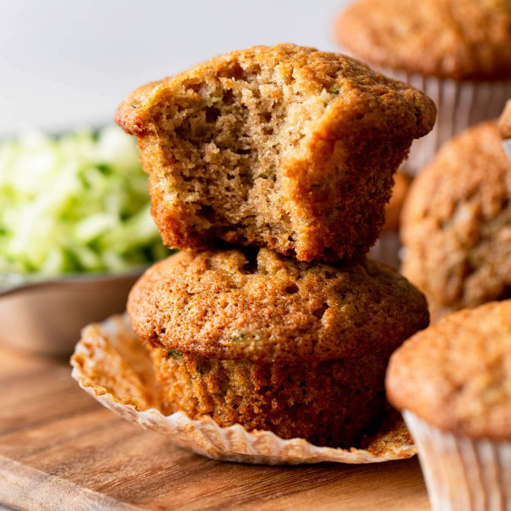 Two zucchini bread muffins stacked on top of each other. The top muffin has a bite missing.