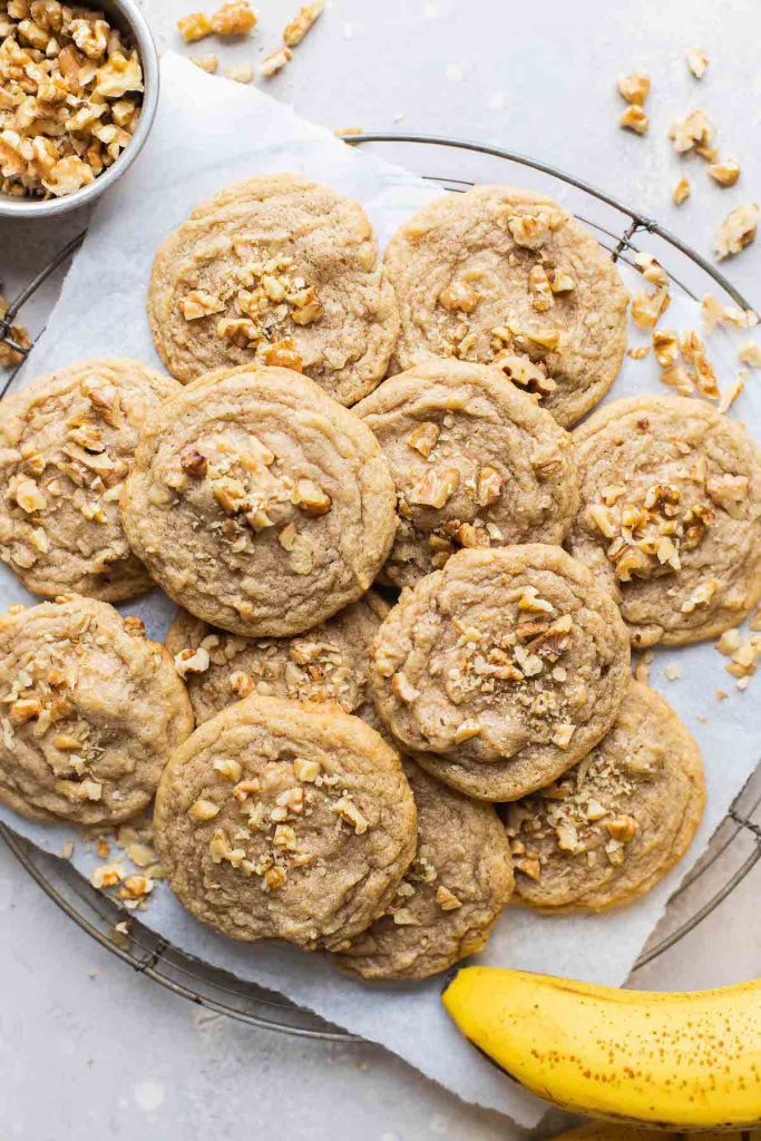 An overhead view of a pile of banana nut cookies on a wire cooling rack. Chopped walnuts are scattered around the cookies. A banana rests on the side.