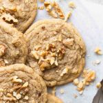 Several banana cookies on a wire rack with a piece of parchment paper underneath them. Pieces of chopped walnuts are scatter on top of and around the cookies.