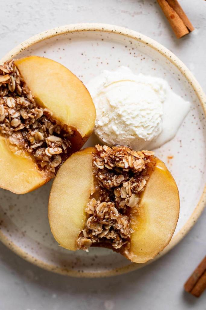 An overhead view of a baked apple that's been cut in half to show the oat filling. A scoop of ice cream is also on the speckled plate.
