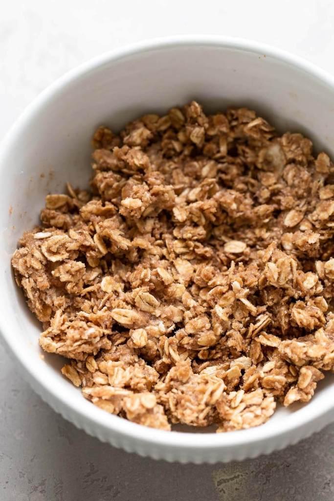 A white bowl full of oatmeal crisp mixture.