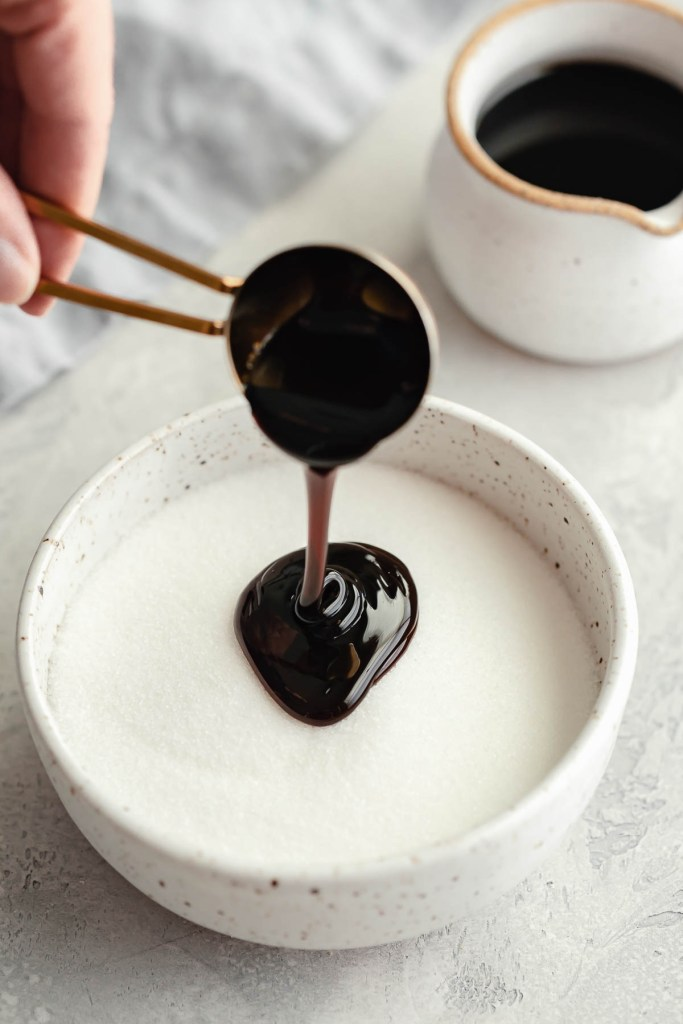 Molasses being poured into a bowl of granulated sugar. A small jug of molasses rests in the background.