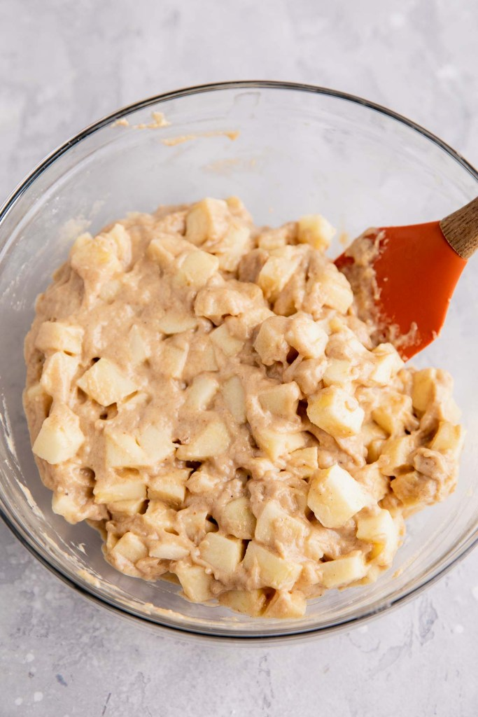 An overhead view of apple fritter dough in a glass mixing bowl with a rubber spatula.
