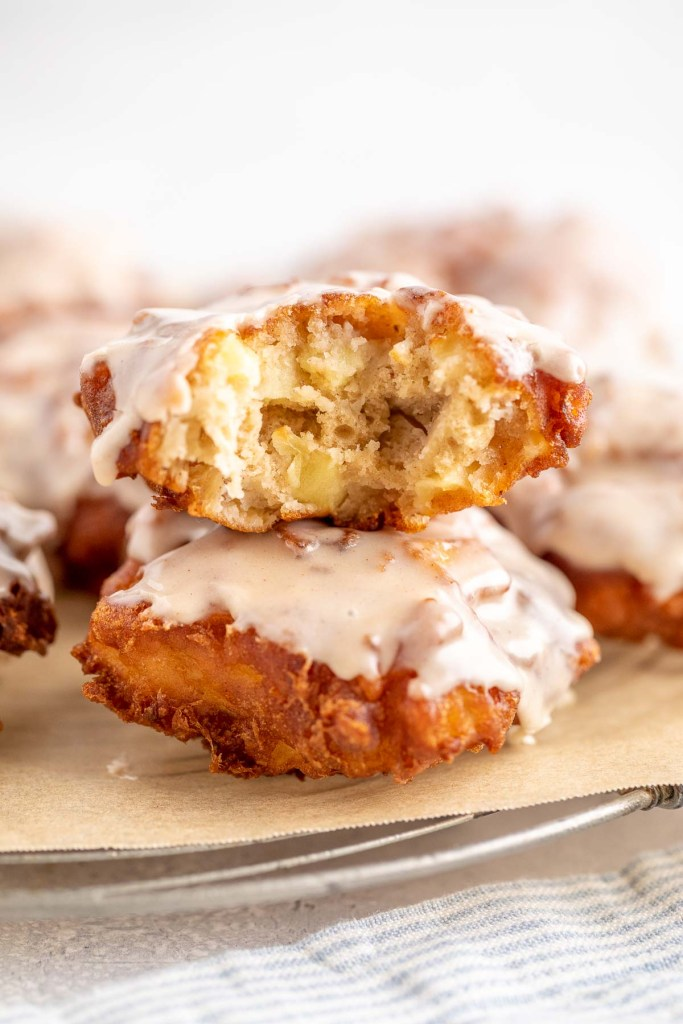 Two apple fritters, stacked on top of each other. The top fritter has a bite missing.