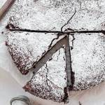 An overhead view of a flourless chocolate cake topped with powdered sugar. Two slices have been cut from the cake and one is being removed.